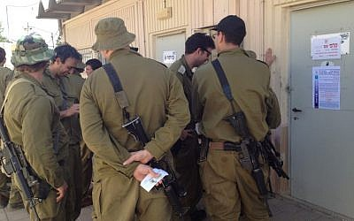 Reserve soldiers lining up to vote Tuesday at a base in central Israel. (photo credit: Times of Israel Staff)