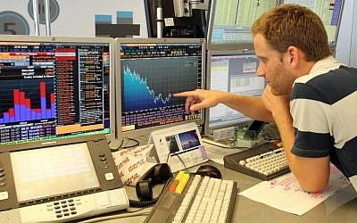 An analyst checks the numbers on the Tel Aviv Stock Exchange (Photo credit Meir Partush/Flash90)