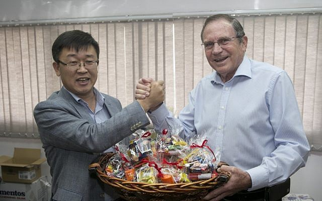 (L to R) D.S. Choi, CEO of Samsung Israel, and Uri Slonim, chairman of Variety Israel, with one of Samsung's Purim baskets (Photo credit: Eran Lam)