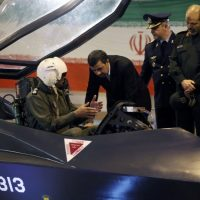 Former Iranian President Mahmoud Ahmadinejad, center, listens to an unidentified pilot during a ceremony to unveil Iran's newest fighter jet, the Qaher-313, in Tehran, Iran, February 2, 2013 (AP/Mehr News Agency/Younes Khani)
