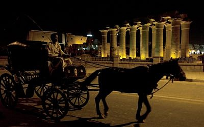 A horse-drawn carriage passing by the Luxor Temple on Tuesday. (photo credit: AP/Nasser Nasser)