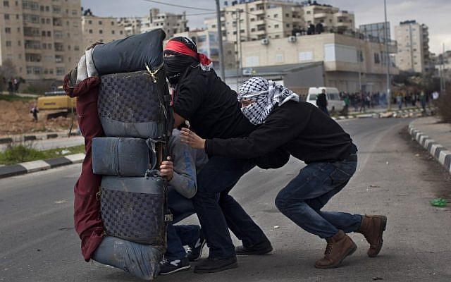 Masked Palestinians use a car seat as a shield during a protest to support Palestinian prisoners, outside the Ofer Prison near the West Bank city of Ramallah, Tuesday, Feb. 19 (photo credit: AP/Bernat Armangue)