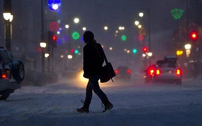 A woman crosses Congress Street during a snowstorm in Portland, Maine, Friday. Snow began falling across the Northeast on Friday, ushering in what was predicted to be a huge, possibly historic blizzard and sending residents scurrying to stock up on food and gas up their cars. The storm could dump 1 to 3 feet of snow from New York City to Boston and beyond. (AP Photo/Robert F. Bukaty)