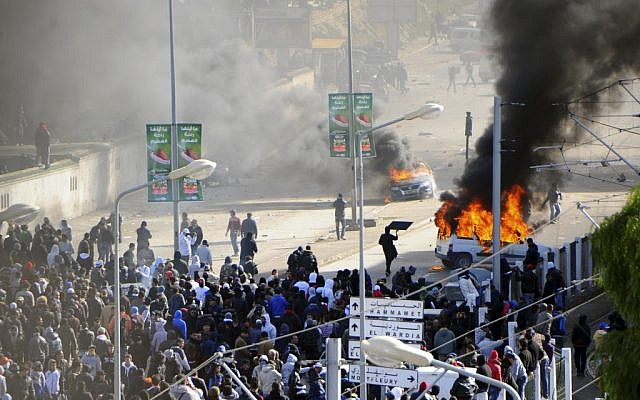 Cars burn next to the cemetery where thousands of Tunisians are gathered at el Jallez cemetery to attend the funerals of slain opposition leader Chokri Belaid, near Tunis, Friday Feb. 8 (photo credit: AP/Hassene Dridi)