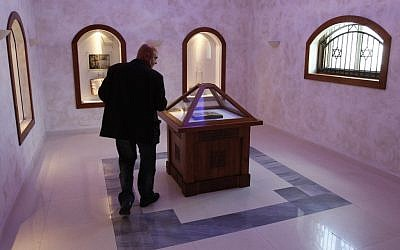 Bosnian conservationist technician Hamo Karkelja looks at original book of Sarajevo Haggadah, displayed at the National Museum of Bosnia and Herzegovina in Sarajevo, Bosnia, 2010 (photo credit: Amel Emric/AP)