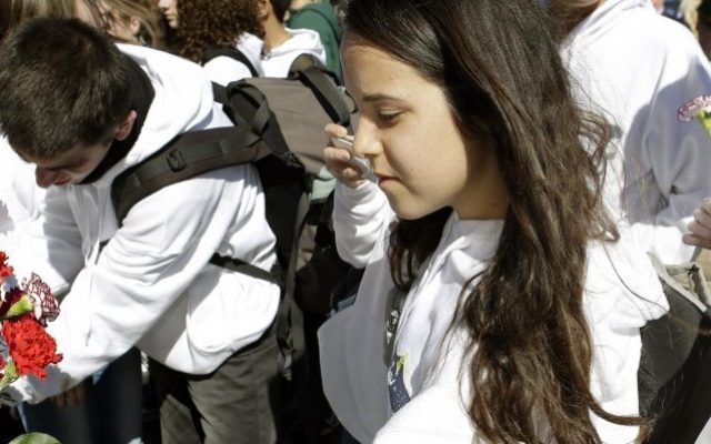 Noa Assa, front, along with fellow students from the Mekif Alef High School in Beersheba place flowers on a gate in front of the Space Mirror Memorial during a remembrance ceremony on the 10th anniversary of the loss of space shuttle Columbia crew at the Kennedy Space Center Visitor Complex, Friday, at Cape Canaveral, Fla. A few hundred people gathered there to remember the Columbia seven, which included the first Israeli spaceman Ilan Ramon. (photo credit: AP Photo/John Raoux)