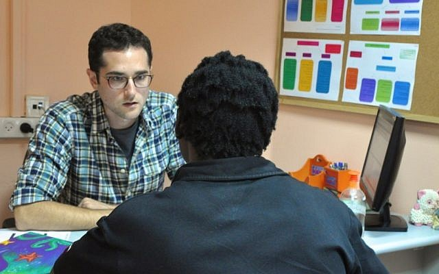 Jonah Mink, the founder of the MigrantHealth:IL public health pilot program, speaks to a patient from Eritrea at the Tel Aviv Refugee Clinic (photo credit: Michal Shmulovich/Times of Israel)