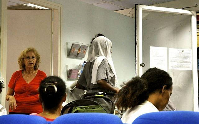 Asylum-seeking women (their faces purposely hidden to hide their identities) and a volunteer nurse at the Tel Aviv Refugee Clinic (photo credit: Michal Shmulovich/Times of Israel)