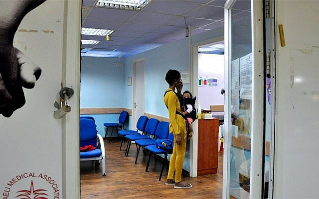An asylum-seeking woman from Eritrea inquires about medical services for her and her child at the Tel Aviv Refugee Clinic (photo credit: Michal Shmulovich/Times of Israel)