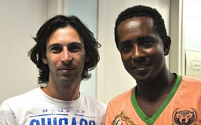 Orel Ben Ari, left, the head of the Tel Aviv Refugee Clinic (the Public Clinic), pictured with a young Eritrean man who had fled to Israel after sustaining several physical and emotional traumas in Egypt, including the loss of his hand, before being granted asylum in Europe. (photo credit: Michal Shmulovich/Times of Israel)