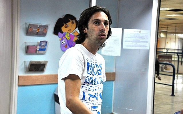 Orel Ben Ari stays late to sort out volunteers, donations, and other day-to-day aspects of running the Tel Aviv Refugee Clinic (photo credit: Michal Shmulovich/Times of Israel)