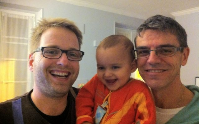 Eran, left, and partner Jean-Louis embrace son Elay-Gabriel at their Paris home. The French government doesn't give citizenship to children with gay surrogate parents. (Courtesy of Eran via JTA)