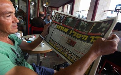 A man reading a news report about the reported Mabhouh assassination in 2010. (photo credit: Kobi Gideon/Flash90)