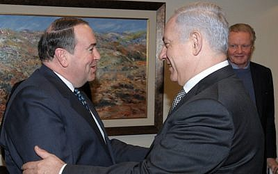 Former Arkansas governor Mike Huckabee meets Prime Minister Benjamin Netanyahu in Jerusalem during a 2011 visit (with actor Jon Voight in the background). (Photo credit: Amos BenGershom/ GPO/Flash90)