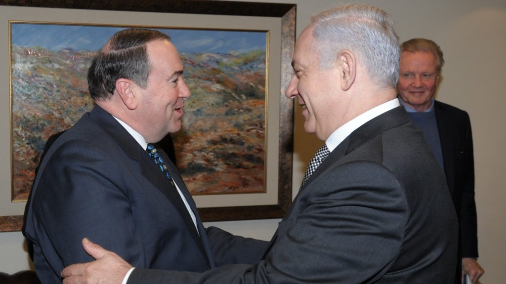 Former Arkansas governor Mike Huckabee meets Prime Minister Benjamin Netanyahu in Jerusalem on a 2011 visit (with actor Jon Voight in the background). (Photo credit: Amos BenGershom/ GPO/Flash90)