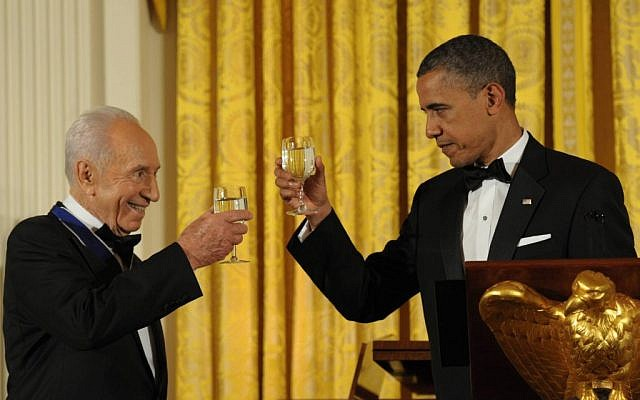 Obama and Peres toasting at the ceremony where Obama presented Peres the Presidential Medal of Freedom in June. Peres will return the favor when Obama visits Israel in March (photo credit: Amos Ben Gershom/ GPO/Flash90)