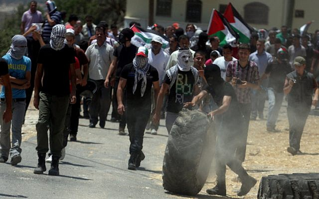 Palestinian protesters throw stones at Israeli security forces during clashes near Nablus in July 2012. (photo credit: Issam Rimawi/Flash90)