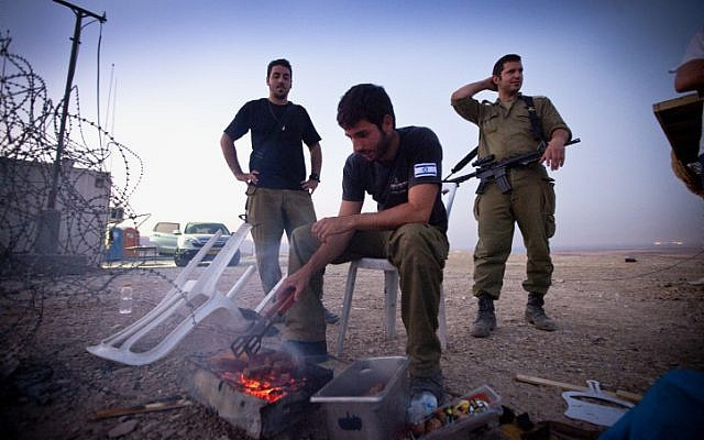 Want to join them? Maariv reports on a new donation program that allows tourists to visit IDF bases and eat with the soldiers. These soldiers prepare a meal while at an observation post by the Dead Sea in 2012 (photo credit: Moshe Shai/FLASH90)
