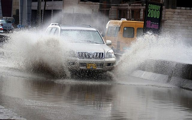 Illustrative photo of a car driving on a flooded street (photo credit: Issam Rimawi/Flash90)