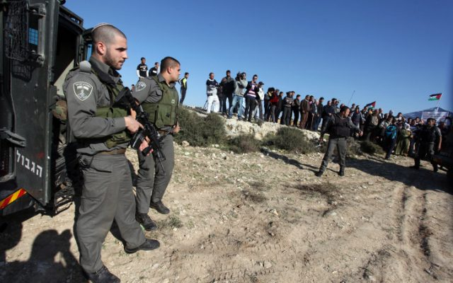 An Israeli border policeman stands in front of Palestinian activists in preparation to removing an outpost, January 19, 2013. (photo credit: Issam Rimawi/Flash90)
