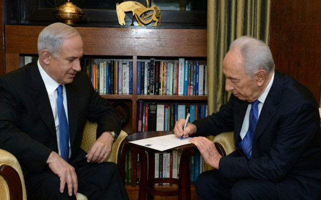 President Shimon Peres signs the formal document charging Prime Minister Benjamin Netanyahu with forming the next government, at a ceremony at the President's Residence, February 02, 2013. (Photo credit: Kobi Gideon / GPO/FLASH90)