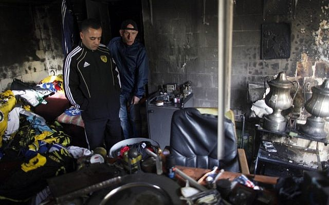 Members of the Beitar Jeursalem soccer club inspect the team's administrative offices after unknown arsonists set it on fire. (photo credit: Flash90)