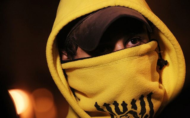 A hooded Beitar Jerusalem fan seen outside the Teddy stadium in Jerusalem ahead of a match on Sunday, February 10 (photo credit: Miriam Alster/Flash90)