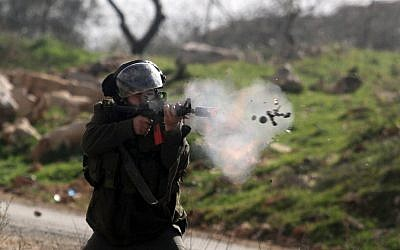 An Israeli soldier fires a smoke grenade at Palestinian protesters during West Bank clashes (photo credit: Issam Rimawi/Flash90)