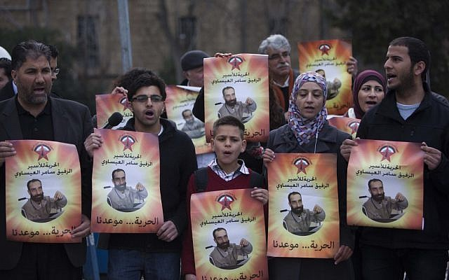 Palestinians holding pictures of Samer Issawi at a protest in Jerusalem on February 19. (photo credit: Yonatan Sindel/Flash90)