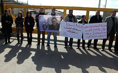Palestinian journalists carry placards during a protest in support of jailed journalists and prisoners on hunger strike in Israeli prisons, in front of Ofer military prison, near the West Bank city of Ramallah, on Wednesday, February 20 (photo credit: Issam Rimawi/Flash90)
