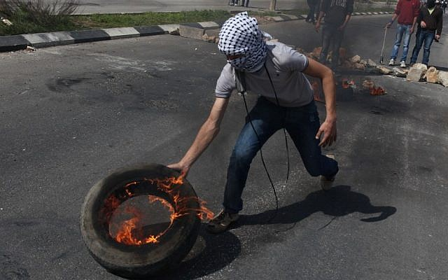 A Palestinian protester rolls a burning tire toward Israeli soldiers during an earlier clash, next to Ofer prison, near the West Bank city of Ramallah (photo credit: Issam Rimawi/Flash90)