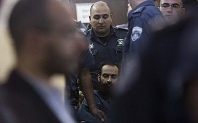 Israeli prison service guards surround Palestinian prisoner Samer Issawi, seated in his wheelchair, into a hearing at the Jerusalem Magistrate's Court on February 21, 2013. (photo credit: Yonatan Sindel/Flash90)