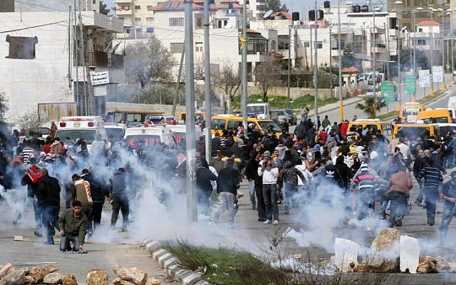 Palestinian protesters dispersed by Israeli security forces during clashes next to Ofer prison, near the West Bank city of Ramallah, on February 22 (photo credit: Issam Rimawi/Flash90)