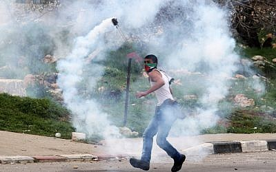 A Palestinian protester uses a slingshot to hurl back a tear gas canister fired by Israeli security forces during clashes next to Ofer prison, near the West Bank city of Ramallah, on February 22, 2013. (photo credit: Issam Rimawi/Flash90)