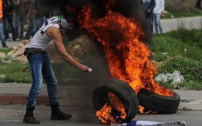 A Palestinian protester stands next to a burning tire during clashes with Israeli security forces next to Ofer prison, near the West Bank city of Ramallah, February 22, 2013, (photo credit: Issam Rimawi/Flash90)