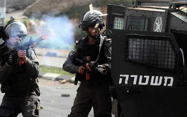 An Israeli border policeman fires rubber bullets at stone-throwing Palestinian protesters during clashes outside Israel's Ofer military prison near the West Bank city of Ramallah, February 24, 2013 (photo credit: Issam Rimawi/Flash90)