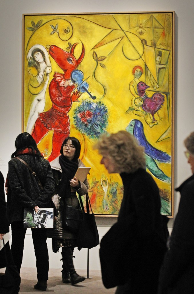 Members of the media stand in front of: La Danse, a 1952 painting by Russian artist Marc Chagall before the opening of the exhibition: Chagall, between War and Peace, at the Luxembourg museum in Paris, Tuesday Feb. 19, 2013. The exhibition starts February 21 and ends July 21, 2013. (photo credit: AP/Remy de la Mauviniere)