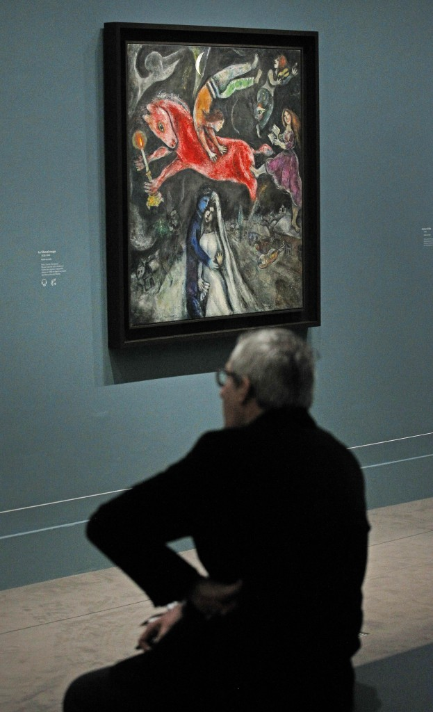 A member of the media sits next to 1944, Le Cheval Rouge, a painting by Russian artist Marc Chagall before the opening of the exhibition: Chagall, between War and Peace, at the Luxembourg museum in Paris, Tuesday Feb. 19, 2013. The exhibition starts February 21 and ends July 21, 2013. (photo credit: AP/Remy de la Mauviniere)