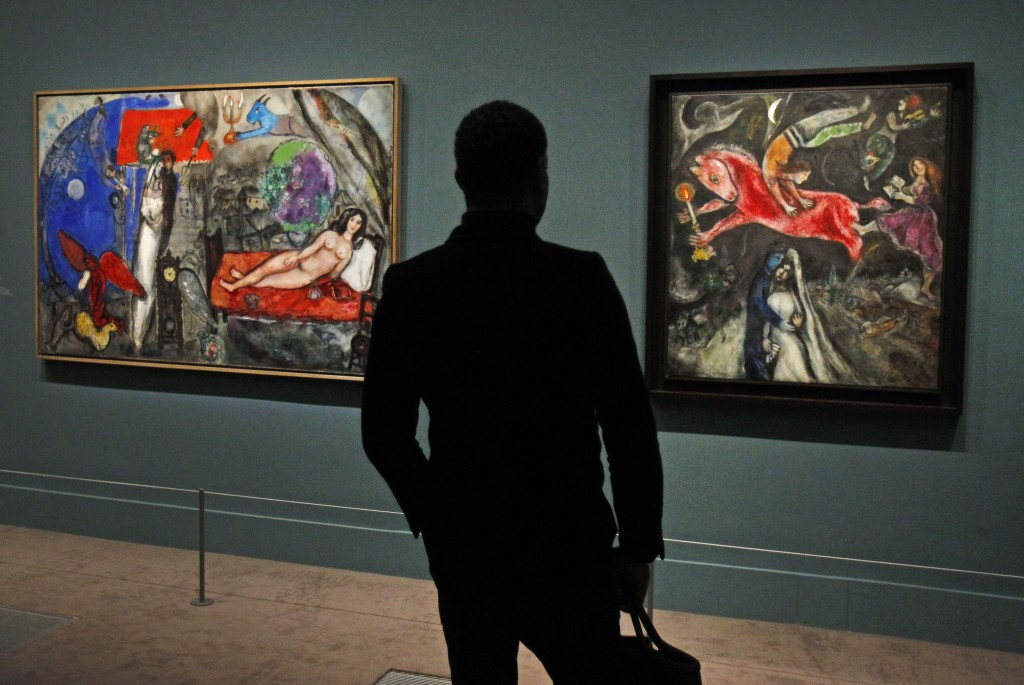 A member of the media views a painting by Russian artist Marc Chagall before the opening of the exhibition: Chagall, between War and Peace, at the Luxembourg museum in Paris, Tuesday Feb. 19, 2013. The exhibition starts February 21 and ends July 21, 2013. Painting at right is: 1944, Le Cheval Rouge, and at left: 1944, A Ma Femme. (photo credit: AP/Remy de la Mauviniere)