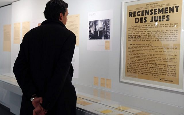 "A man looks at a poster reading ""Census of Jews"" displayed in an exhibition at the Shoah Memorial in Paris, Tuesday, Feb. 12, 2013. The French state prepares to give back seven stolen Nazi-era paintings - 4 of which are in the Louvre - to two Jewish families, after a decade-long tug of war. (photo credit: AP/Jacques Brinon)"