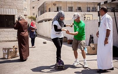 A Palestinian girl gets a little help from Israeli pro longboarder Yoni Ettinger (photo credit: Yair Hasidof)