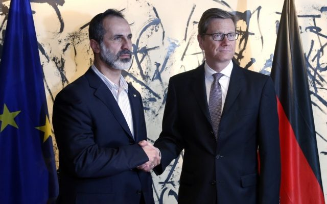 German Foreign Minister Guido Westerwelle, right, and Sheikh Mouaz Al-Khatib, president of the National Coalition of Syrian Revolutionary and Opposition Forces, shake hands during the Security Conference in Munich on Friday. (photo credit: Matthias Schrader/AP)