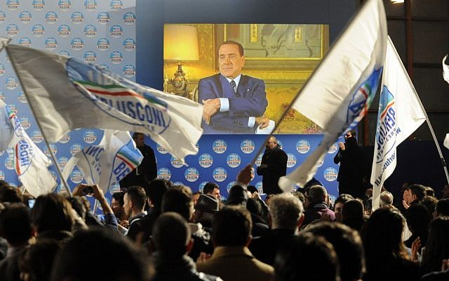 Supporters wave flags in front of a giant monitor broadcasting a message by Silvio Berlusconi during a center-right coalition rally in Naples, Italy, Friday, Feb. 22, 2013 (photo credit: AP/Salvatore Laporta)