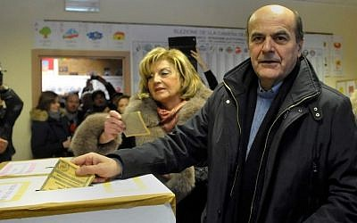 Pier Luigi Bersani, right, leader of the Democratic Party, casts his ballot with his wife Daniela, Sunday. (AP Photo/Marco Vasini)