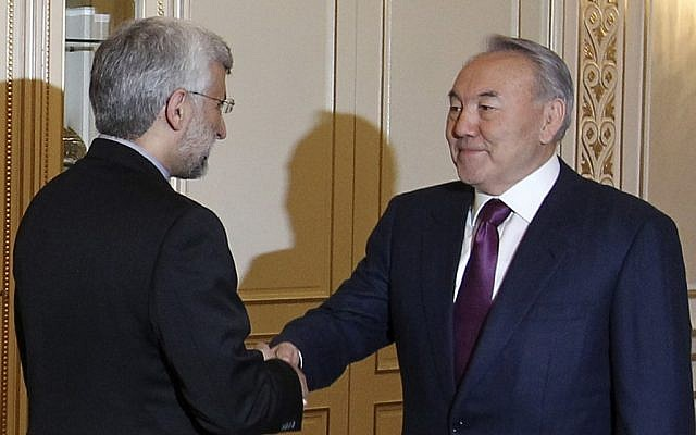 Chief Iranian nuclear negotiator Saeed Jalili, left, shakes hands with Kazakhstan's President Nursultan Nazarbayev prior to their talks in Almaty, Kazakhstan, Monday.(photo credit: AP/Pavel Mikheyev)