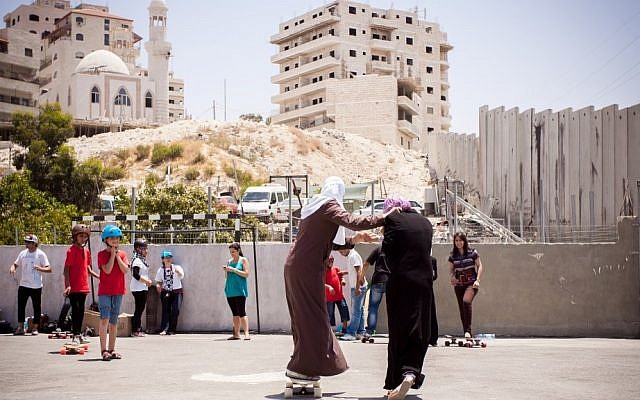 Teenage girls practice gliding on longboards at the Shuafat refugee camp last July (photo credit: Yair Hasidof)