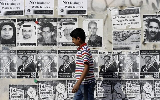 A Bahraini boy walks by a wall with signs in English and Arabic objecting to a government-mediated dialogue between opponents and supporters of the Bahraini monarchy in Sitra, Bahrain, on Saturday, Feb. 9, 2013. (photo credit:AP/Hasan Jamali)