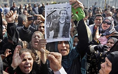 Egyptian relatives of Mohammed el-Gindy, a 28-year-old activist, who died of wounds sustained during clashes near the presidential palace, display his picture as they shout anti-president Morsi slogans during his funeral procession in Tahrir Square, Cairo, on February 4. (photo credit: Amr Nabil/AP)