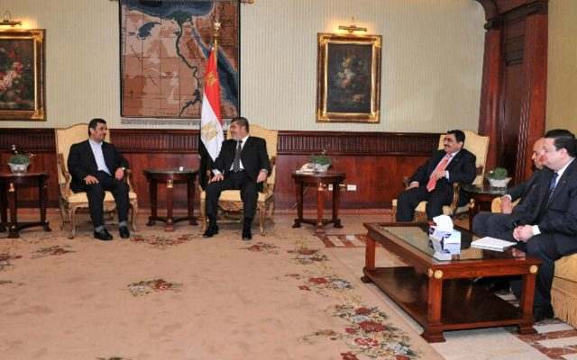 Iran's President Mahmoud Ahmadinejad, left, and Egyptian President Mohammed Morsi, center, meet in Cairo, Egypt, Tuesday, February 5 (photo credit: AP/Egyptian Presidency)