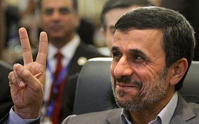 Iran's President Mahmoud Ahmadinejad flashes the victory sign as he attends the 12th summit of the Organization of Islamic Cooperation in Cairo, Egypt, Wednesday, Feb. 6, 2013 (photo credit: AP/Amr Nabil)